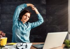 Business woman wearing denim shirt stretching arms in the office